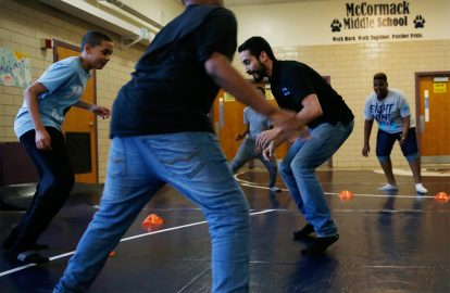 Wrestling coach Jose Valenzuela, center, founded a nonprofit wrestling program for city kids.